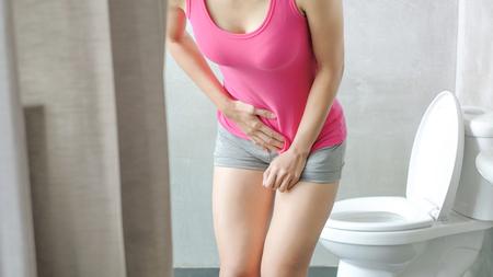 Foto de woman with urine urgency in the toilet - Imagen libre de derechos