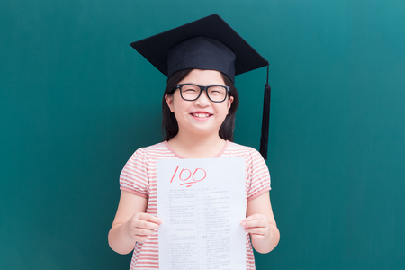 Photo for cute girl get test with full score on blank green chalkboard - Royalty Free Image