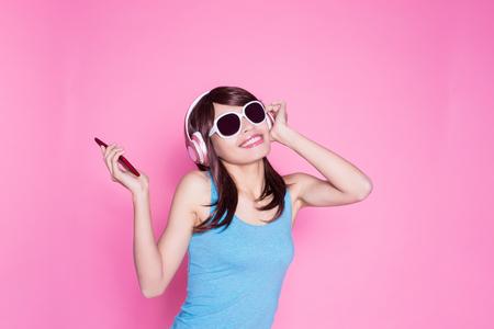Foto de woman use phone listen music on the pink background - Imagen libre de derechos