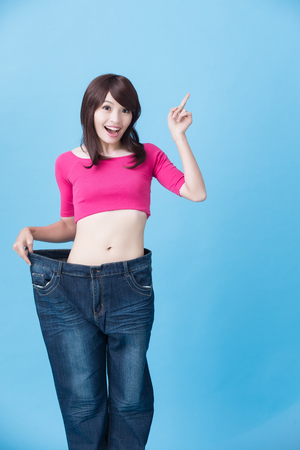Photo for woman introduction somewhere and show weight loss on the blue background - Royalty Free Image