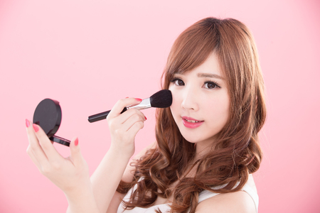 Foto de beauty woman take makeup brush on the pink background - Imagen libre de derechos