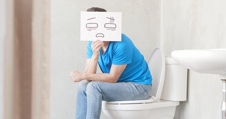 Foto de man take confuse billboard with constipation in the toilet - Imagen libre de derechos