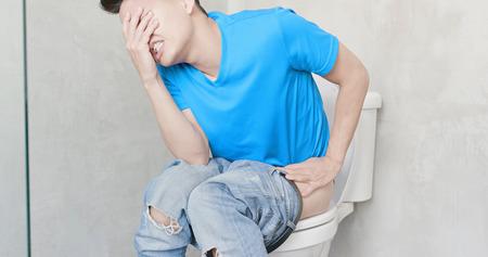 Foto de man feel pain with constipation in wc - Imagen libre de derechos