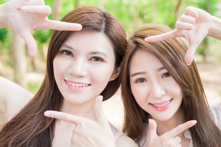 Foto de two beauty woman smile happily with brace and making frame gesture - Imagen libre de derechos