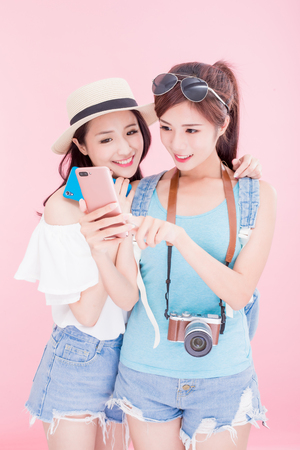 Photo for two travel woman smile happily and use phone on the pink bakcground - Royalty Free Image