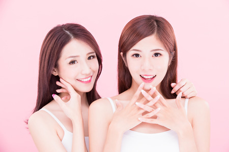 Photo pour two beauty skincare women with health tooth on the pink background - image libre de droit