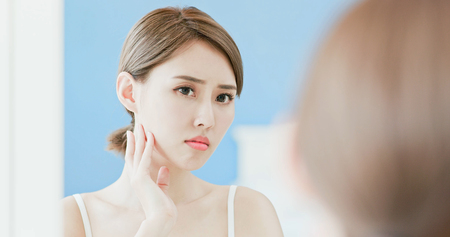 Photo for woman look mirrior feel upset and touch her face with acne problem - Royalty Free Image