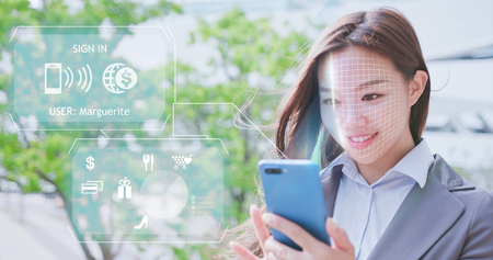 Photo for Asian business woman is shopping on smart phone with scanning facial recognition. - Royalty Free Image