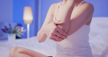 Photo pour beauty woman apply cream with elbow on the bed at night - image libre de droit