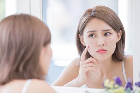 Foto de woman look mirrior feel upset and touch her face with acne problem - Imagen libre de derechos