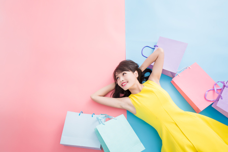 Foto de woman take shopping bag happily and look copy space on the blue and pink background - Imagen libre de derechos