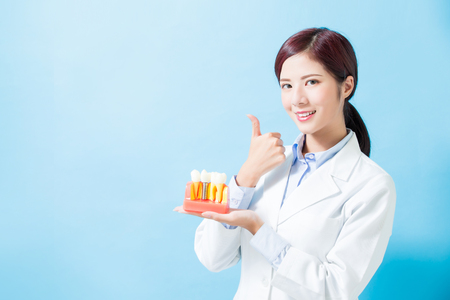 Foto de woman dentist take implant tooth and thumb up on the blue background - Imagen libre de derechos