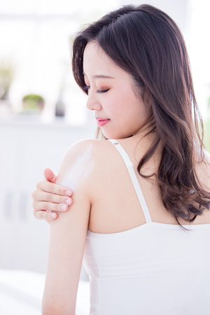Photo pour Young skin care woman applying body lotion on arm and shoulder at home - image libre de droit