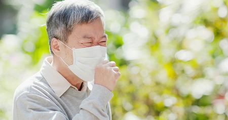 Foto de old man wear mask and cough outdoor - Imagen libre de derechos