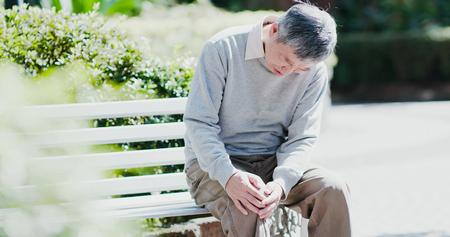 Photo pour old man with a knee problem in the park - image libre de droit