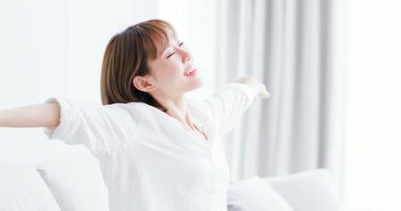 Foto de young woman feel carefree and stretch arm to take a deep breath at home - Imagen libre de derechos