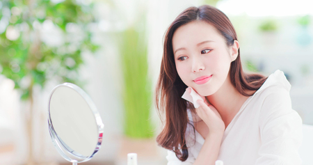 Photo for Smile asian woman remove makeup by Cleansing Cotton and look mirror at home - Royalty Free Image