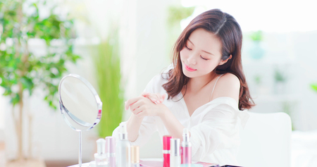 Photo for Young beauty asian woman applying hand cream at home - Royalty Free Image