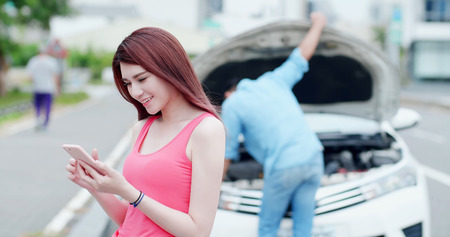 Photo for young woman using mobile phone and feel easy about broken down car on street - Royalty Free Image