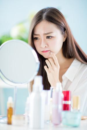 Photo pour asian woman look mirror with acne problem at home - image libre de droit