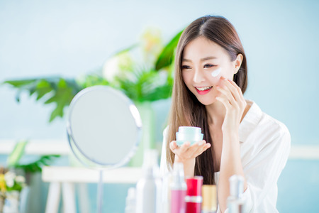 Foto de beauty asian woman apply lotion on her face at home - Imagen libre de derechos