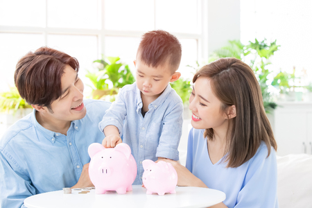 Photo pour Family saving money and putting coins into piggy bank - image libre de droit