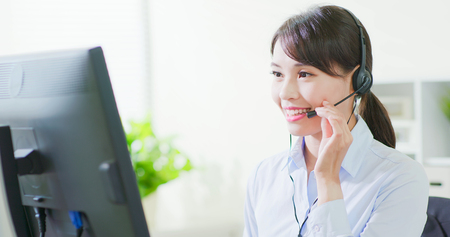 Foto de Young friendly operator woman agent with headsets working in call center - Imagen libre de derechos