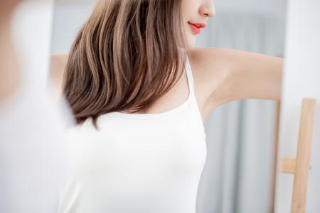 Foto de Young beauty woman smile with clean underarm in front of mirror - Imagen libre de derechos