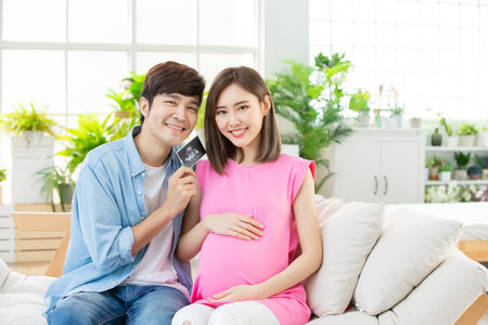 Photo pour happy pregnant woman with husband at home and show the baby ultrasound photo - image libre de droit