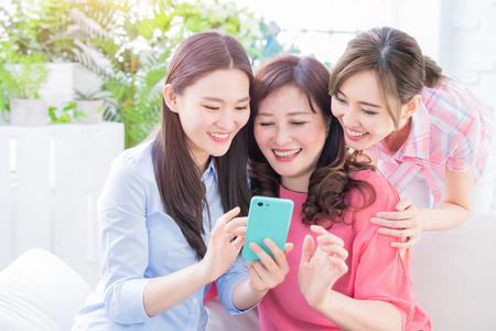 Foto de Daughters and mother use smart phone happily at home - Imagen libre de derechos