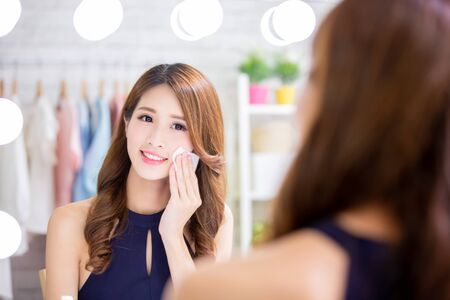 Photo for Close up of smile asian beauty woman moisturizing by cleansing cotton and look mirror - Royalty Free Image