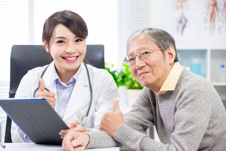 Foto de Female doctor with elder patient show thumbs up - Imagen libre de derechos