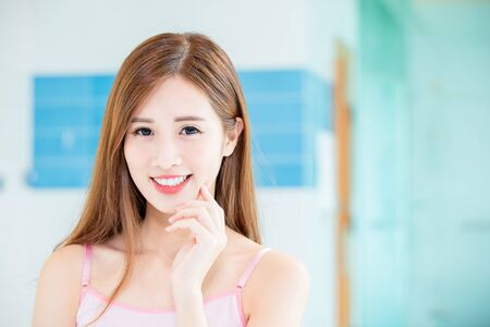Foto de Beauty skin care woman touch her chin and smile to you at home - Imagen libre de derechos