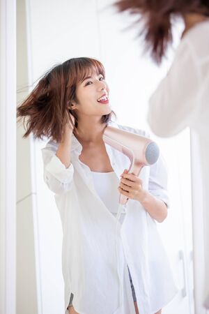 Photo pour beautiful young woman drying her hair with dryer - image libre de droit
