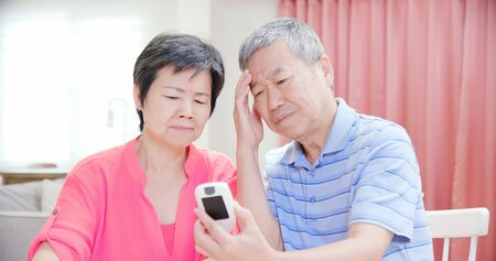 Foto per asian elder couple use blood glucose meter and worry about it - Prevention diabetes concept - Immagine Royalty Free