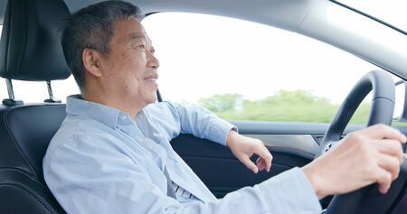 Photo pour asian elderly man driving happily in the car on highway - image libre de droit