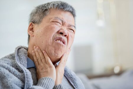 Photo pour close up of asian elderly sick man has sore throat and feel very uncomfortable at home - image libre de droit
