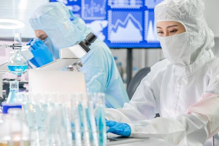 Photo for Asian scientist type computer with cleanroom suit in laboratory - Royalty Free Image