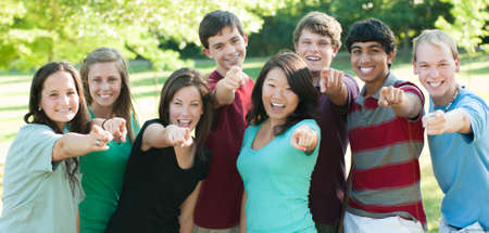 A multi-ethnic group of teenage friends outside pointing