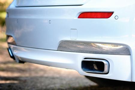 Foto de Selective focus on parking sensor exhaust pipe bumper at rear of white luxurious car bumper close up on light  blurred background. - Imagen libre de derechos
