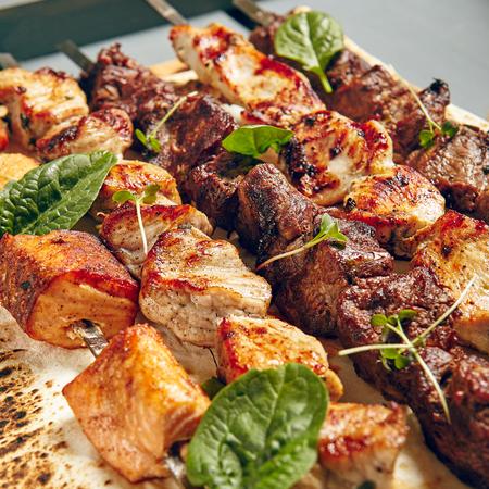 Foto de Chicken, Salmon and Meat Shish Kebabs on Parchment with Sauces - Imagen libre de derechos