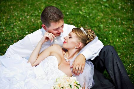 Photo for Happy bride and groom on grass in park - Royalty Free Image