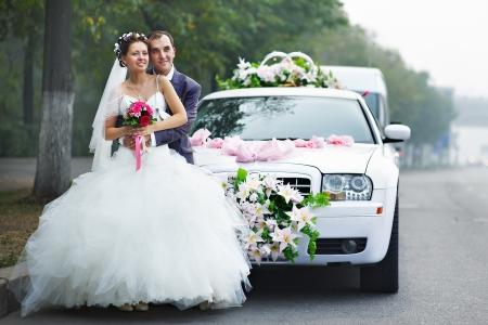 Photo pour Happy bride and groom near wedding limo - image libre de droit