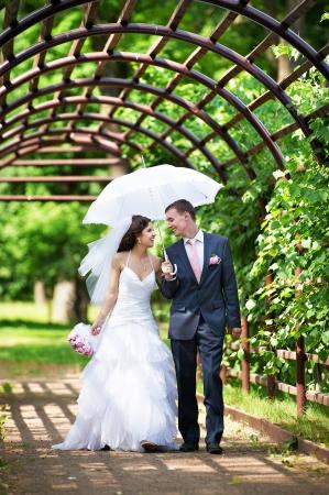 Foto de Happy bride and groom goes along the arch on wedding walk - Imagen libre de derechos