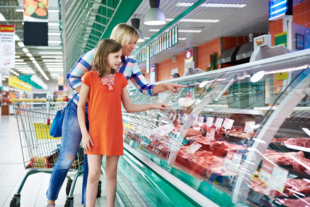 Photo for Mother and daughter chooses a meat in the supermarket - Royalty Free Image