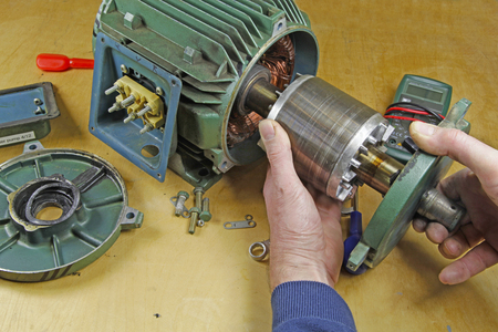 Foto de Three phase induction   motor bearing repair – A fitter/technician  removing rotor from stator  prior to changing shaft bearings - Imagen libre de derechos
