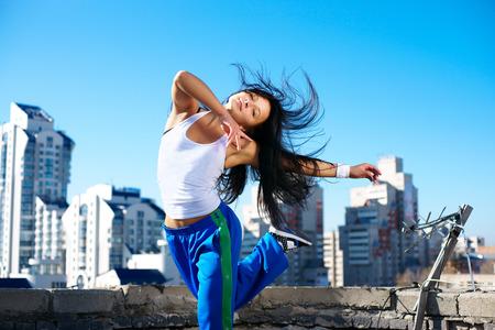 Foto de fitness dancing girl on the roof blue sky - Imagen libre de derechos
