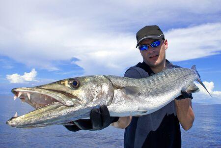Photo pour Deep sea fishing, Catch of fish, big game fishing, Lucky  fisherman holding a giant barracuda - image libre de droit