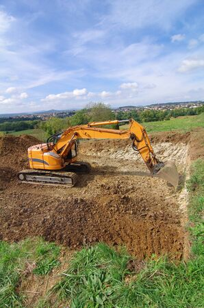 Photo pour Excavator machine in action during earth moving works. Excavator, earthworks, house construction - image libre de droit