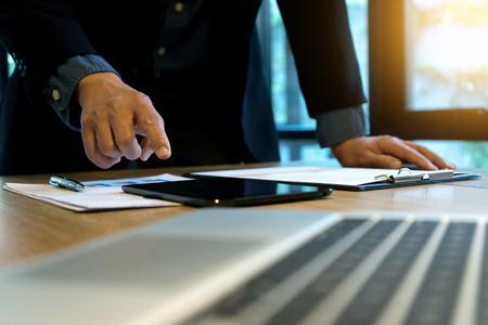Foto de businessman boss stand and use tablet and computer for plan company work. - Imagen libre de derechos